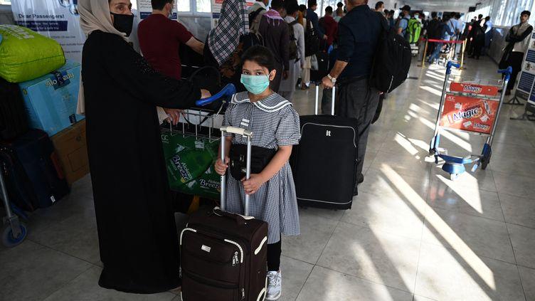Des ressortissants français, des Afghans travaillant à l'ambassade de France et leurs familles patientent avant d'embarquer à bord du dernier vol pour Paris, à l'aéroport international de Kaboul, ce samedi 17 juillet. (SAJJAD HUSSAIN / AFP)