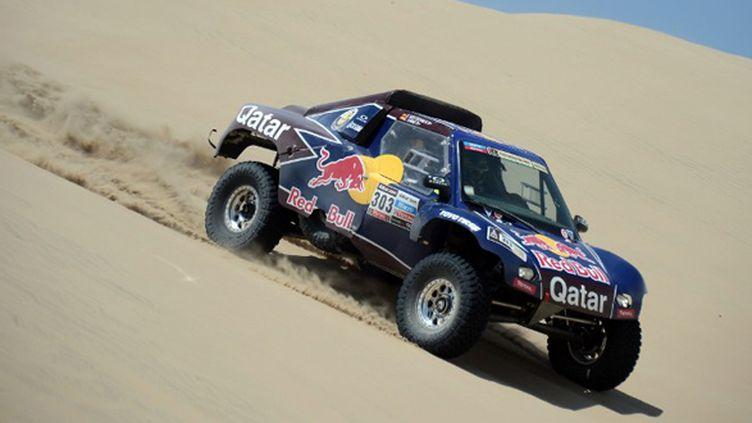 Carlos Sainz (Qatar Red Bull) descend une dune (FRANCK FIFE / AFP)