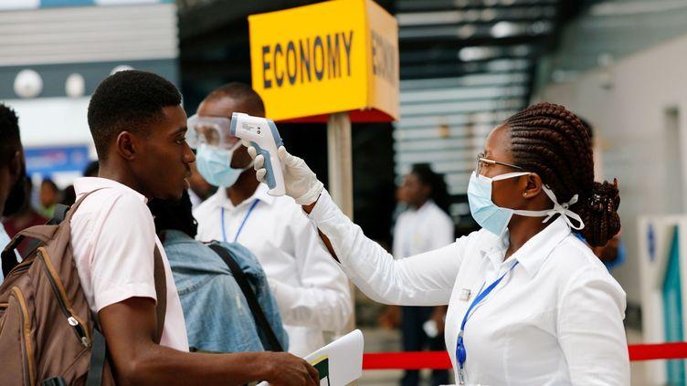 Un agent de santé vérifie la température d'un voyageur dans le cadre de la procédure de dépistage des coronavirus à l'aéroport international de Kotoka à Accra au Ghana, le 30 janvier 2020 (FRANCIS KOKOROKO / Reuters)