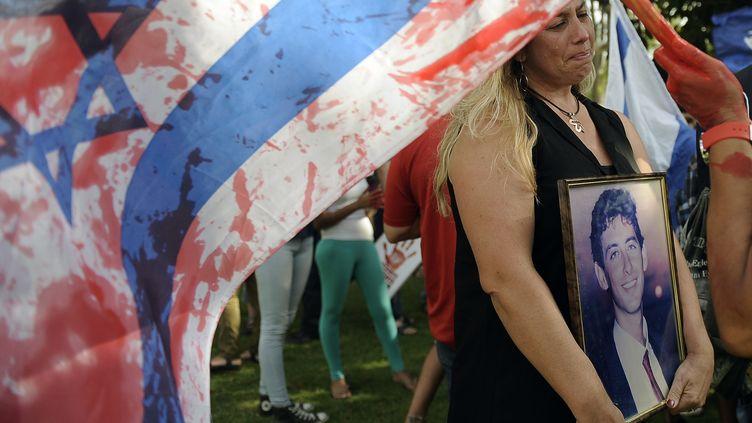 Une Israélienne se tient près d'un drapeau israélien couvert de faux sang, le 12 août 2013, à Tel Aviv (Israël), lors d'une manifestation contre la libération de prisonniers palestiniens. (DAVID BUIMOVITCH / AFP)
