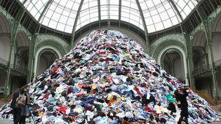 Au centre de la nef se trouve une montagne de vêtements au sommet duquel un grappin en prélève quelques uns avant de les relâcher. Dans tout l'espace, des haut-parleurs diffusent l'enregistrement des battements de cœurs. Saisissant. (GINIES / SIPA)