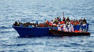 Une équipe du Migrant Offshore Aid Station (MOAS) secourt une embarcation de migrants en Méditerranée, le 8 septembre 2014. (AFP PHOTO / MOAS / HO)