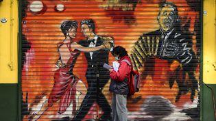 Un homme portant un masque devant un mural représentant des danseurs de tango à Buenos Aires, le 8 mai 2020. (RONALDO SCHEMIDT / AFP)