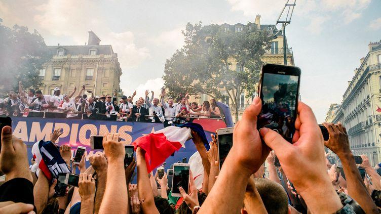Des supporters acclament le bus des Bleus revenus victorieuxde la Coupe du monde. L'équipe de France a défilé à Paris, le 16 juillet 2018. (SIMON GUILLEMIN / HANS LUCAS)