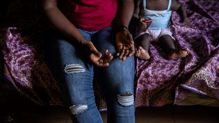 Une femme et son enfant se reposent le 26 juin 2019 à Benin City, dans l'un des centres d'hébergement de la Société pour l'autonomisation des jeunes (SEYP), une organisation qui réhabilite et réintègre les femmes revenant de Libye portant souvent des enfants en bas âge, résultat de viol. (FATI ABUBAKAR / AFP)