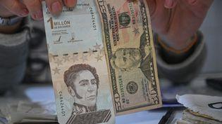 Un billet de la monnaie vénézuélienne, le bolivar, à côté d'un billet de 50 dollars américain. (FEDERICO PARRA / AFP)
