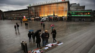 Des passants lisent les pancartes antisexistes laissées devant la gare de Cologne, le 11 janvier 2016, deux semaines après la vague d'agressions sexuelles du Nouvel An. (OLIVER BERG / DPA / AFP)