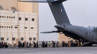Des personnes évacuées de Kaboul débarquent à la base militaire française de Al Dhafra, à Abou Dhabi (Emirats Arabes Unis), le 23 août 2021. (BERTRAND GUAY / AFP)