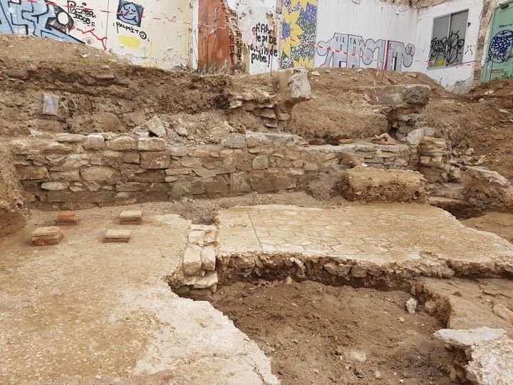 Tranche 2. Deux pièces d'une domus datée des Ier/IIe siècles de notre ère. On a découvert dans l'une, à gauche sur le cliché, des pilettes d'hypocauste permettant la circulation d'air chaud sous le sol (disparu) qu'elles soutenaient. À droite, le sol de la pièce voisine présente un décor géométrique en nid d'abeille fait de tesselles noires. Au premier plan, une grande fosse d'époque moderne a recoupé ces bétons de sols antiques en faisant disparaître l'accès qui reliait les deux pièces. (CHARLOTTE GLEIZE / INRAP)