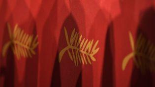 Le logo de la Palme d'or du Festival de Cannes sur rideau rouge. (ANNE-CHRISTINE POUJOULAT / AFP)