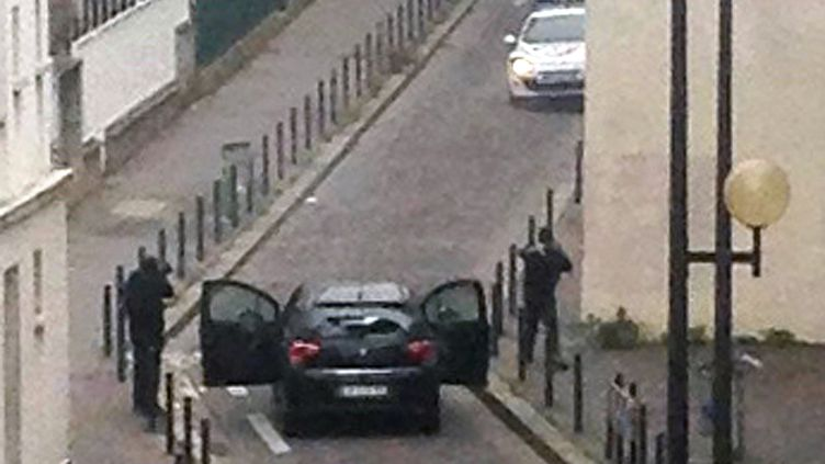 """Des hommes armés et cagoulés ont ouvert le feu dans les locaux de """"Charlie Hebdo"""", mercredi 7 janvier 2015, à Paris. (ANNE GELBARD / AFP)"""