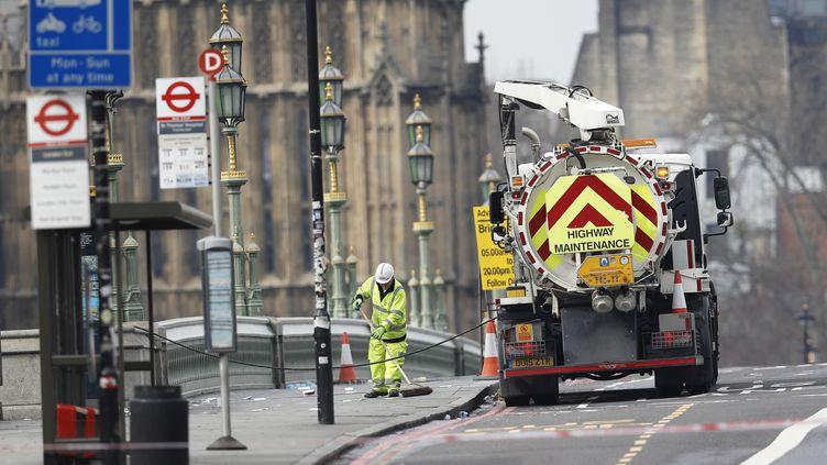Des employés nettoient le pont de Westminster, jeudi 23 mars 2017 à Londres (Royaume-Uni), où plusieurs piétons ont été fauchés par une voiture la veille. (DARREN STAPLES / REUTERS)