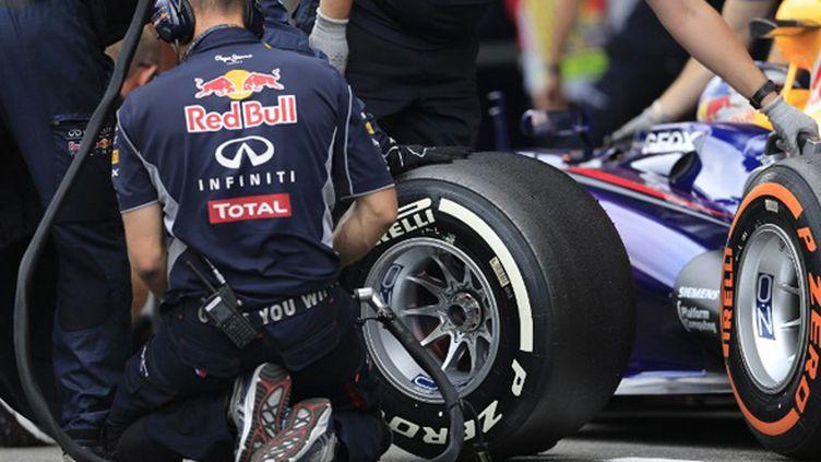 Un mécanicien change un pneu sur la Red Bull (ALEXANDER KLEIN / AFP)