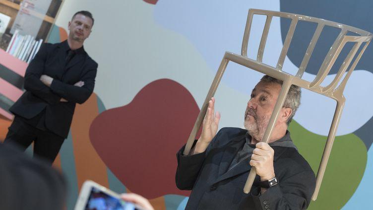 Philippe Starck sur le stand Kartell avec l'une de ses réalisations au Salon du meuble de Milan le 4 avril 2017.  (MIGUEL MEDINA / AFP)