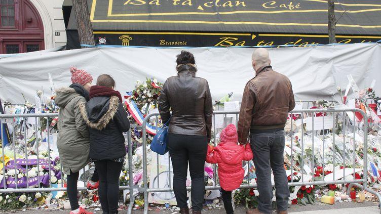 Un groupe rend hommage aux victimes des attentats du 13 novembre, devant le Bataclan, à Paris, le 13 décembre2015. (MATTHIEU ALEXANDRE / AFP)
