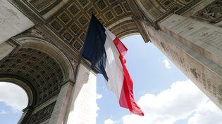 Ledrapeau français flotte sous l'Arc de Triomphe à Paris, le 7 mai 2015,lors dela cérémonie marquant le 70ème anniversaire de la fin de la guerre,le 8 mai 1945. (THOMAS SAMSON / AFP)