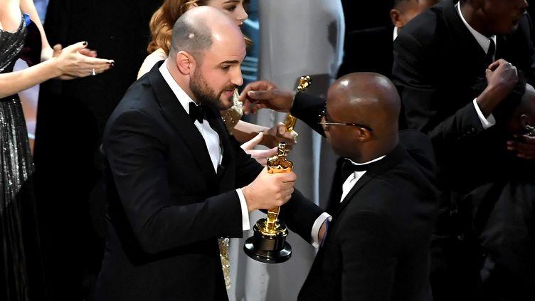 """Le producteur de """"La La Land"""", Jordan Horowitz, tend l'Oscar du meilleur film à Barry Jenkins, réalisateur de """"Moonlight"""", après un cafouillage lors de la cérémonie, le 26 février 2017 à Los Angeles (Etats-Unis). (KEVIN WINTER / GETTY IMAGES NORTH AMERICA / AFP)"""