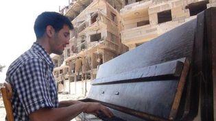 Ayham Al-Ahmad au piano, le 26 juin 2014, dans le camp de réfugiés palestiniens de Yarmouk (Syrie). (RAMI AL-SAYED / AFP)