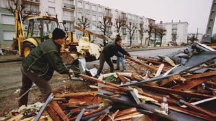 Des employés municipaux de Saint-Pierre-sur-Dives s'activent, le 27 décembre 1999, pour ramasser des débris au lendemain de la tempête qui a touché le nord de la France. (MYCHELE DANIAU / AFP)