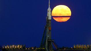 """La """"super lune"""" émerge derrière la fusée Soyuz, à Baikonour (Kazakstan), le 14 novembre 2016. (SHAMIL ZHUMATOV / REUTERS)"""
