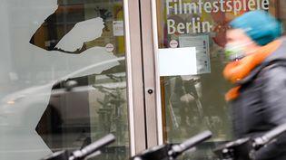 """Une passante masquée devant l'entrée d'un bâtiment, Potsdamer Platz, où l'on peut lire """"Festival international du film de Berlin"""" et voir la reproduction de la silhouette d'un ours, emblème de la Berlinale, le 11 décembre 2020 à Berlin. (JENS KALAENE / DPA / MaxPPP)"""