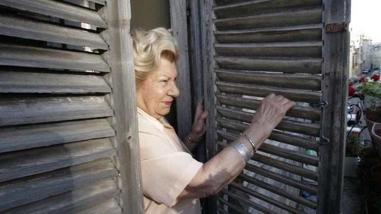 Une femme ferme les volets de son appartement, en juin 2006 à Bordeaux (Gironde). (MICHEL GANGNE / AFP)