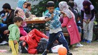 Des enfants jouent dans un centre d'accueil pour demandeurs d'asile près de la gare de Munich, dans le sud de l'Allemagne, le 13 septembre 2015. (ANDREAS GEBERT / DPA / AFP)