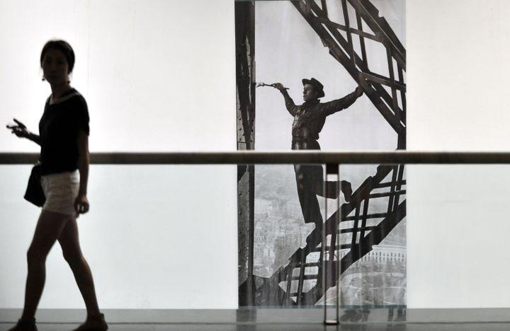 """Une femme devant la photogrpahie """"Le Peintre de la tour Eiffel"""", lors d'une rétrospective de Marc Riboud, à Guangzhou (Chine), le 25 lai 2012. (CHEN YEHUA / XINHUA / AFP)"""