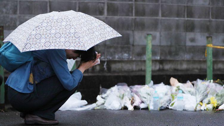 Une femme se recueille, le 19 juillet 2019, devant un autel pour les personnes disparues installé à proximité du studio d'animation incendié jeudi à Kyoto (Japon). (MAMI NAGAOKI / YOMIURI / AFP)