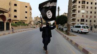 Un membre de l'Etat islamique brandit un drapeau de l'organisation, le 29 juin 2014 à Racca (Syrie). (REUTERS)