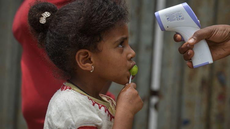 Une enfant éthiopienne dont la température est mesurée durant une campagne de prévention contre le coronavirus à Addis-Abeba, le 20 avril 2020. (MICHAEL TEWELDE / AFP)