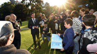 """Le Premier ministre, Manuel Valls, accueille des enfants dans les jardins de Matignon, à Paris, à l'occasion de la """"journée mondiale des oubliés des vacances"""", organisée par le Secours populaire, le 19 août 2015. (MIGUEL MEDINA / AFP)"""
