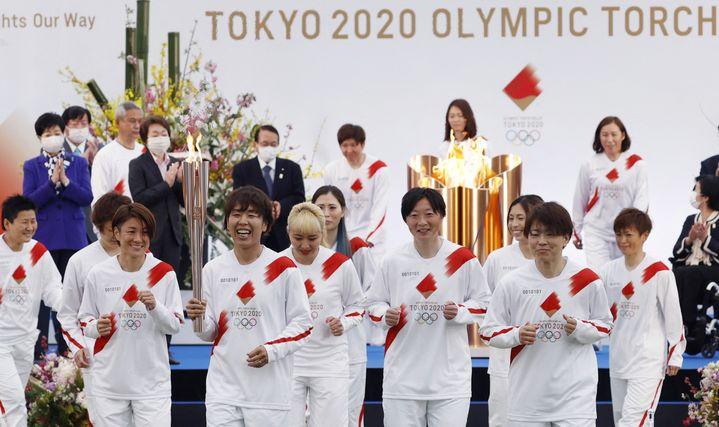 A Naraha (dans la préfecture de Fukushima), le 25 mars 2021, les joueuses de l'équipe nationale de football, championnes du monde en 2011, ont fait partie des premiers porteurs de la flamme olympique. (POOL FOR YOMIURI / YOMIURI /  AFP)