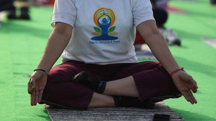 Une femme pratiquant le yoga à New Delhi (Inde). Photo d'illustration. (MONEY SHARMA / AFP)
