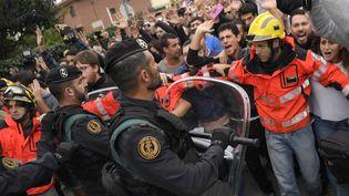 Des pompiers catalans forment un cordon de sécurité entre les manifestants indépendantistes et la police, à Sant Julia de Ramis (Espagne), le 1er octobre 2017. (LLUIS GENE / AFP)