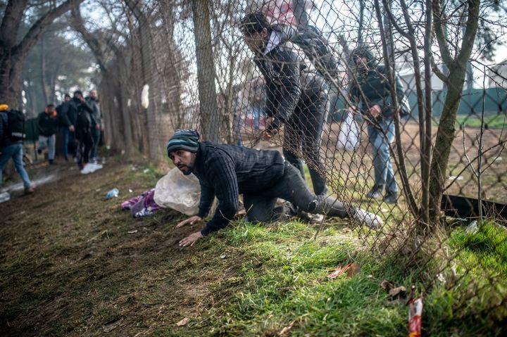 Un migrant traverse une barrière lors d'affrontements avec la police grecque à Pazarkule, dans le district d'Edirne, le 29 février 2020. (BULENT KILIC / AFP)