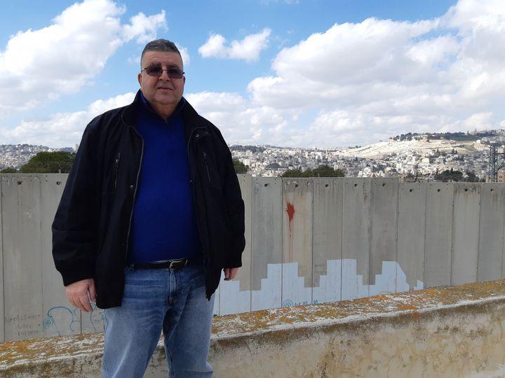 Ahmed Abou Illel, maire d'Abou Dis, pose devant le mur. A trois kilomètres à vol d'oiseau, Jérusalem-Est (FRÉDÉRIC MÉTÉZEAU / RADIO FRANCE)