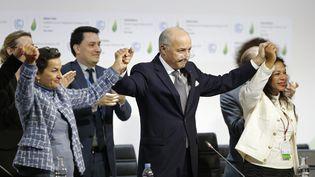 Laurent Fabius (au centre) célèbre l'adoption de l'accord sur le climat arraché samedi 12 décembre au Bourget près de Paris. (STEPHANE MAHE / REUTERS)