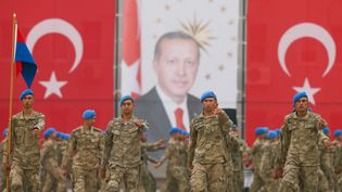 Des soldats turcs paradant lors d'une cérémonie militaire devant le portrait du présidentRecep Tayyip Erdogan, le 18 octobre 2019 à Izmir (Turquie). (EMIN MENGUARSLAN / ANADOLU AGENCY / AFP)