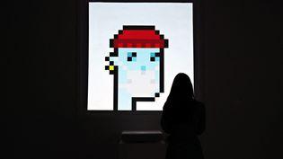 """L'image d'un personnage numérique pixellisé au visage bleu, frappée du certificat d'authenticité """"NFT"""", a été vendue 11,7 millions de dollars à New York chez Sotheby's, juin 2021 (CINDY ORD / GETTY IMAGES NORTH AMERICA)"""