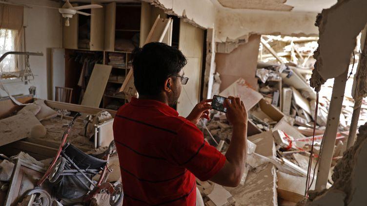 Un Israëlien prend en photo les dégâts d'une maison détruite par un tir de roquette du Hamas, à Ashkelon, près de Gaza, en Israël, mardi 11 mai 2021. (JACK GUEZ / AFP)