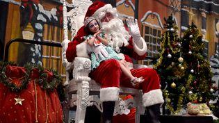 Un homme déguisé en père Noël pose avec une petite fille à Sydney (Australie), le 8 décembre 2015. (SAEED KHAN / AFP)