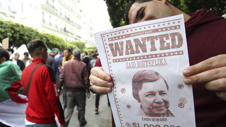 """Un Algérien montre une pancarte """"wanted"""" avec le portrait de Saïd Bouteflika, frère du président déchu, dans une manifestation à Alger, le 19 avril 2019. (AFP)"""