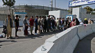 Des Afghans patientent devant une entrée de l'aéroport de Kaboul, le 28 août 2021. (WAKIL KOHSAR / AFP)