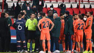 Les joueurs des deux clubs se réunissent autour de l'arbitre pour réclamer des explications, le 8 décembre 2020, au Parc des Princes, à Paris. (FRANCK FIFE / AFP)