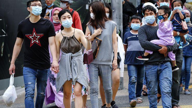 Des Malaisiens portant le masque dans le centre-ville de Kuala Lumpur. (EYEPRESS NEWS / AFP)