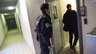 Un policier accompagne un homme au centre de rétention administrative du Canet, à Marseille, le 18 novembre 2017. (BERTRAND LANGLOIS / AFP)