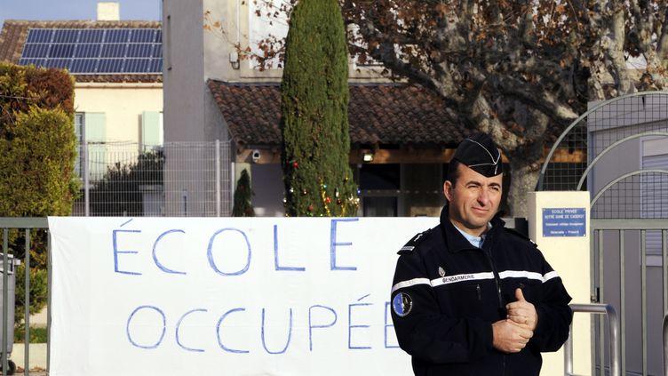 Un gendarme devant l'école Notre-Dame-de-Caderotà Berre-l'Etang (Bouches-du-Rhône), le 7 décembre 2011. (ANNE-CHRISTINE POUJOULAT / AFP)