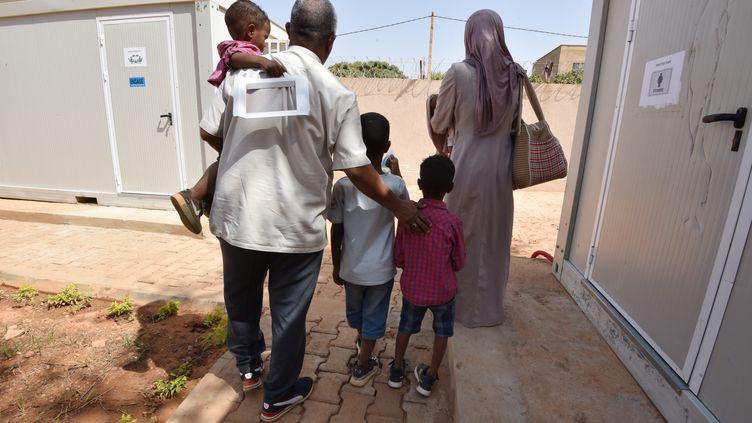 Des réfugiés marchent dans un bâtiment du HCR à Niamey (Niger), le 17 novembre 2017, après avoir été évacués de Libye. (SIA KAMBOU / AFP)