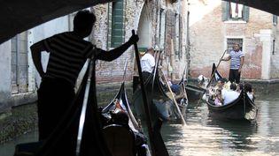 Des touristes visitent Venise (Italie) sur des gondoles, le 10 septembre 2011. (ALESSANDRO BIANCHI / REUTERS)